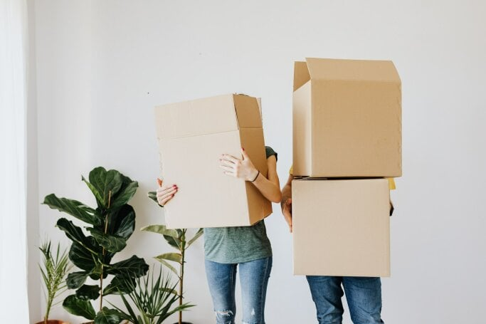 couple-carrying-cardboard-boxes-in-living-room-4506270